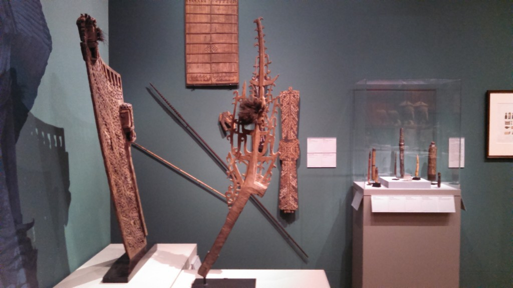 Various artfully crafted utilitarian objects from Cenderawasih Bay including canoe prows and and war shields.