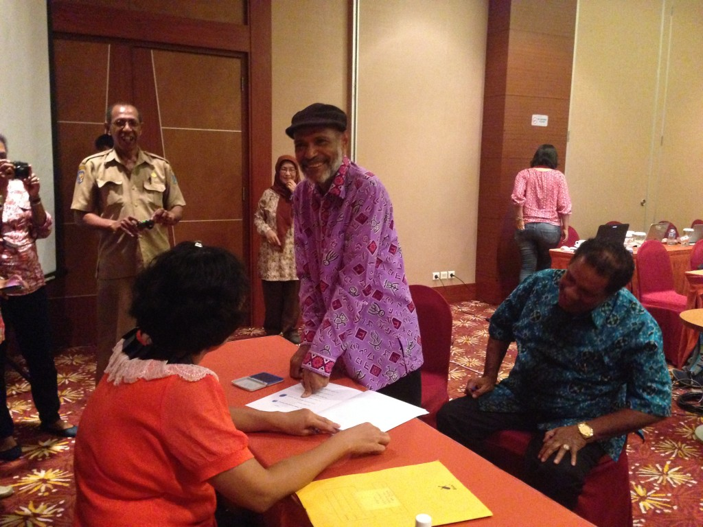 """Reverend Phil Erari and Raja Ampat Regent Marcus Wanma sign the founding documents, marking the beginning of a new journey in conservation for Indonesia's West Papua - """"The Conservation Province""""."""